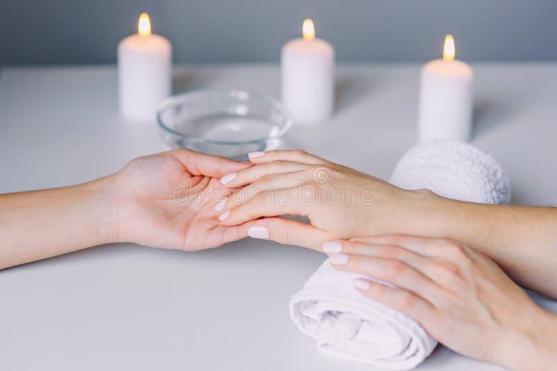 Maniküristhände, die Massage zu den Händen des weiblichen Kunden tun Frauenhand, die Maniküreverfahren empfängt Geschossen vom Ma lizenzfreie stockfotografie