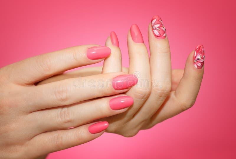 Manikürte Frau ` s Nägel mit rosa nailart mit Blumen lizenzfreie stockbilder
