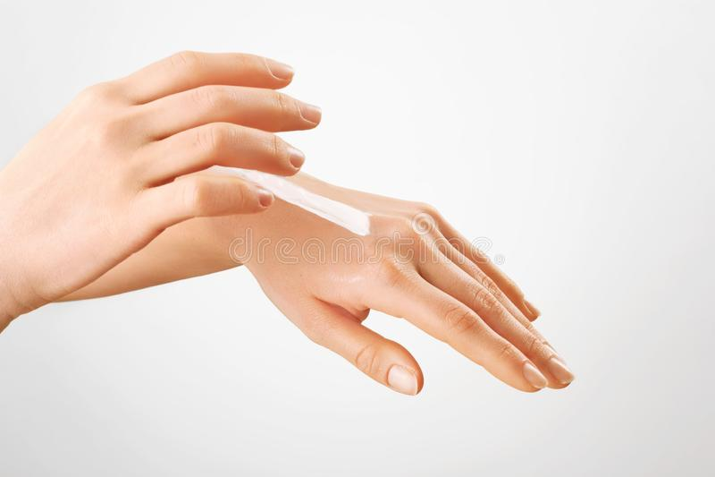 Manikürte Hände mit Feuchtigkeitscreme Handlotion Zutreffen des transparenten Lacks stockbild