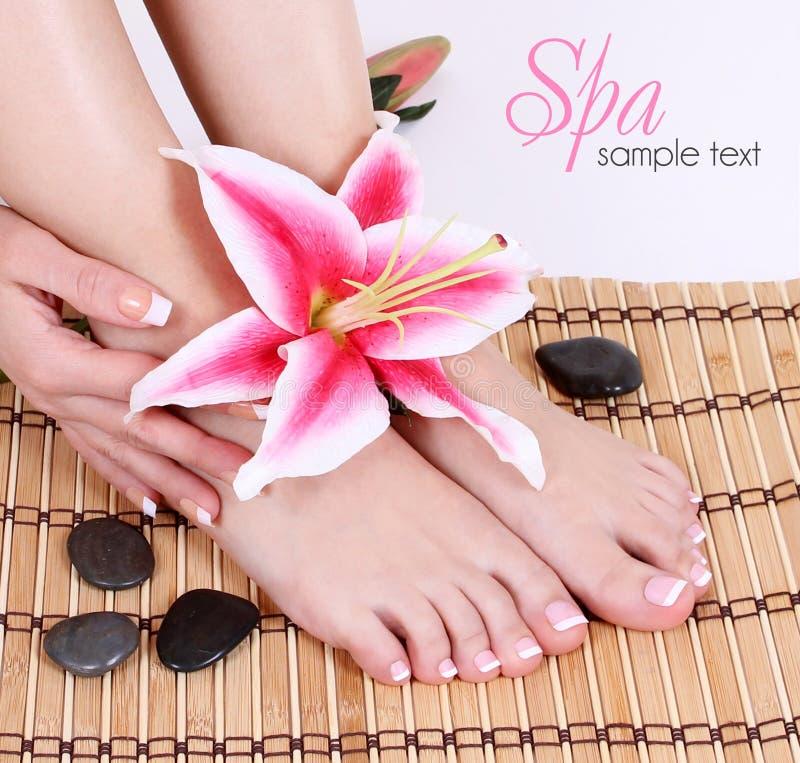 Manikürte weibliche bloße Füße mit rosa Lilienblumen- und -badekurortsteinen über Bambusmatte lizenzfreie stockbilder