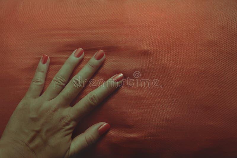 Manikürte weibliche Hand mit Leuchtorange-Nagellack auf zusammenpassendem Kissen lizenzfreies stockfoto