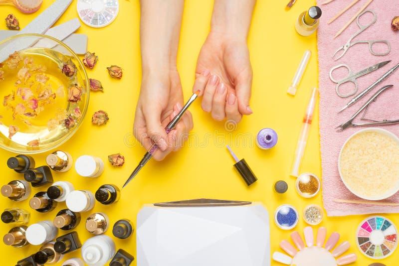 Manik?re - bedeutet f?r die Schaffung, Gelpolituren, alle f?r Nagelpflege, Sch?nheitskonzept, Sorgfalt Auf einem gelben Hintergru lizenzfreies stockbild