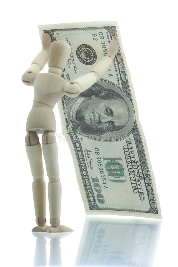 Manikin holds falling dollar bill royalty free stock photography