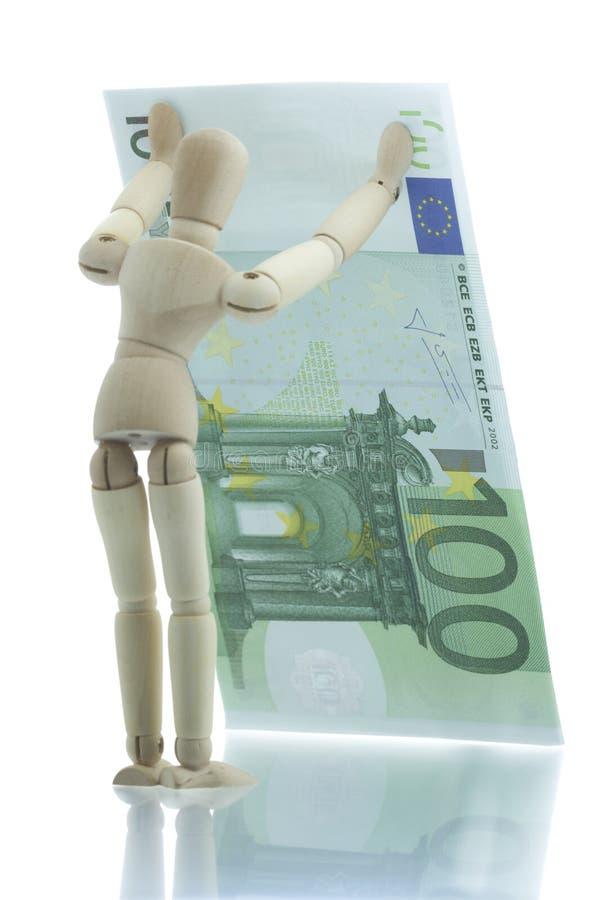 Manikin holds falling euro bill stock photography