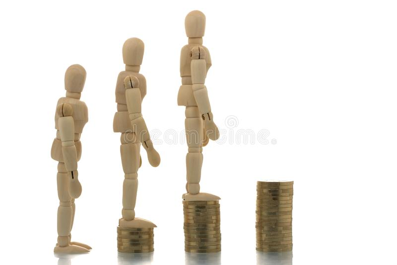 Manikins going up coin piles stock photography