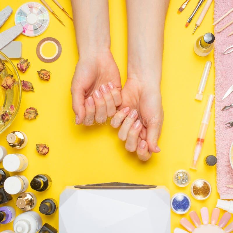 Manikyr-arbete med spikar, skönhetomsorg Kvinnan får en manikyr spikar Kosmetologen sätter spikar till klienten, på gul bakgrund royaltyfria bilder