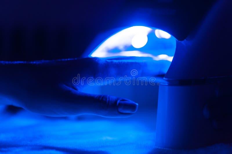 Manikyr i processen som använder den Uv lampan för, spikar royaltyfria foton