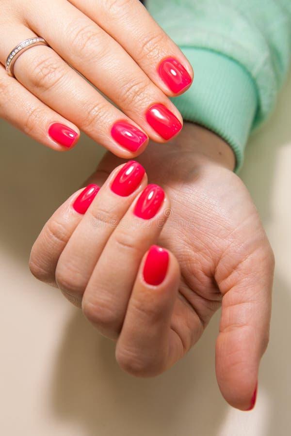 Manikyr - skönhetbehandlingfotoet av trevliga manicured kvinnafingernaglar med rött spikar polermedel arkivfoton