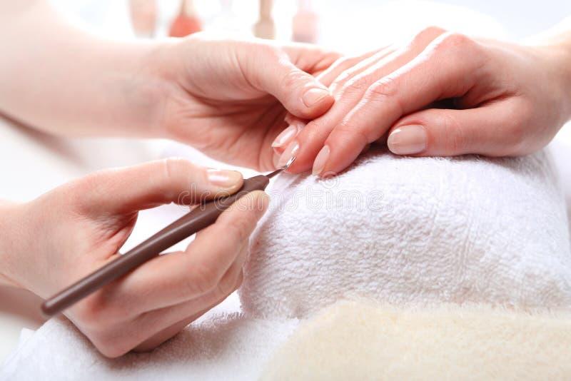 Manikyr som klipper flår kvinnan till en kosmetolog royaltyfri foto