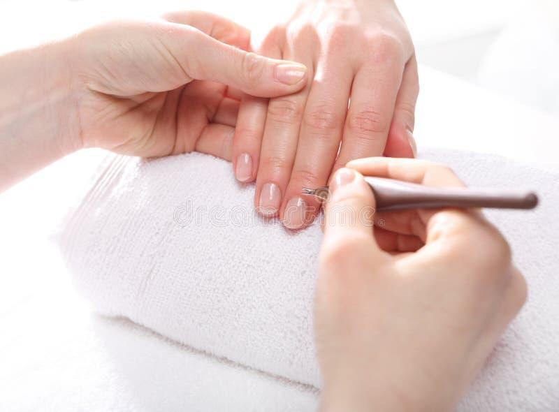 Manikyr som skjuter hudar, en kvinna till en kosmetolog arkivfoton