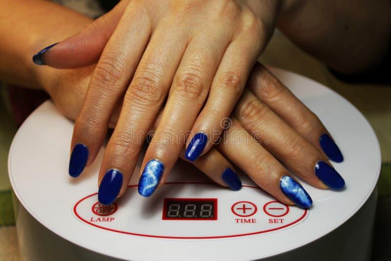 manikyr som utförs av studenten händerna ligger på en special ultraviolett lampa Blått fullföljande med en målad vit blixtlås royaltyfri fotografi