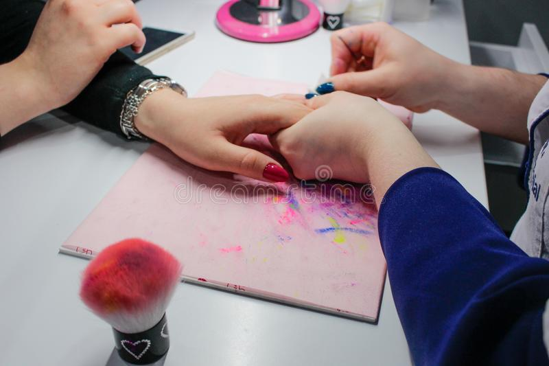 Manikyr spikar målarfärg, Closeupskott av en kvinna i en spikasalong som mottar en manikyr av en kosmetolog fotografering för bildbyråer