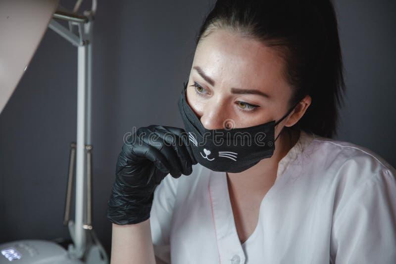 Manikyrist i en svart maskering och svarta handskar som sitter p? arbete Det lyckliga ung flickainnehav h?nger l?s p? en vitbakgr royaltyfri fotografi