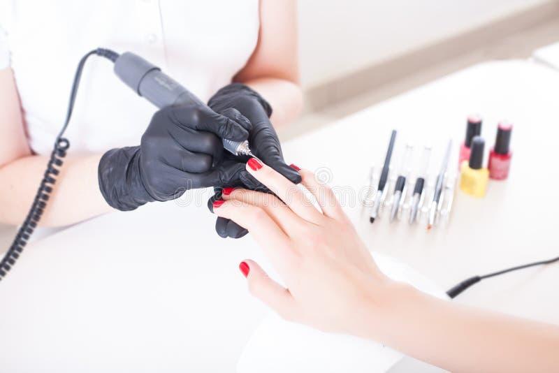 Manikyristen spikar konstnären behandlar spikar med manikyrmalningskäraren skönhetservice, spikar salongen, hälsovård och skönhet royaltyfria bilder