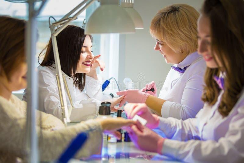 Manikyrister på arbete i skönhetsalongen Räcka omsorg royaltyfri foto
