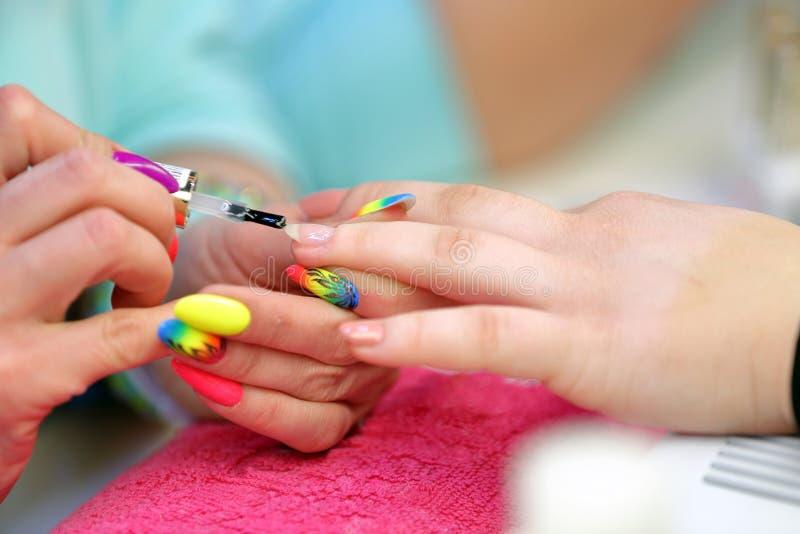 Manikyristförlagen gör manikyr på handen för den unga kvinnan fotografering för bildbyråer