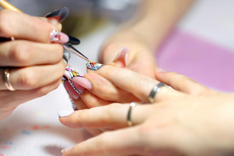 Manikyristförlagen gör manikyr på handen för den unga kvinnan arkivfoto