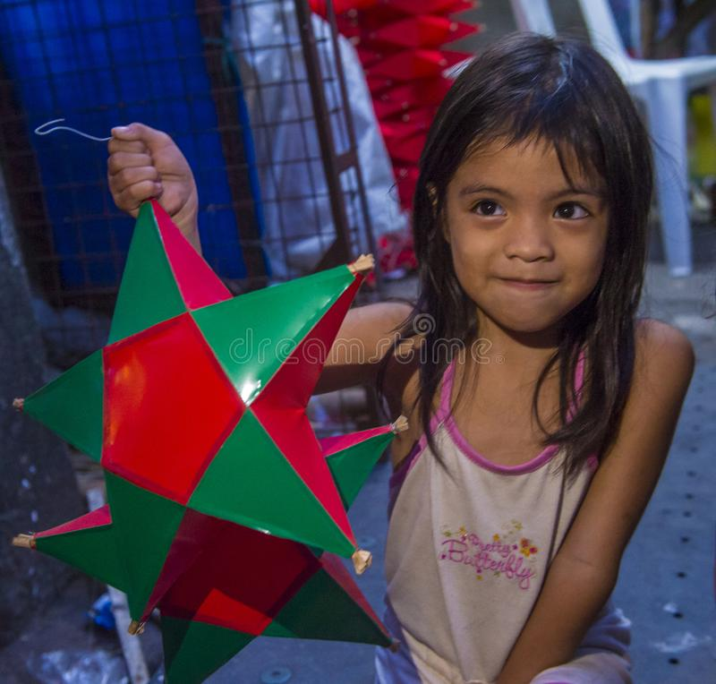 Manila Christmas market lanterns. MANILA , PHILIPPINES - DEC 14 : A Filipino girl holding a lantern in a Christmas market in Las Pinas city , Manila the stock photo