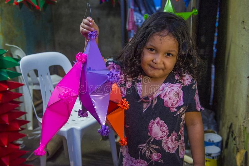 Manila Christmas market lanterns. MANILA , PHILIPPINES - DEC 14 : A Filipino girl holding a lantern in a Christmas market in Las Pinas city , Manila the stock photos