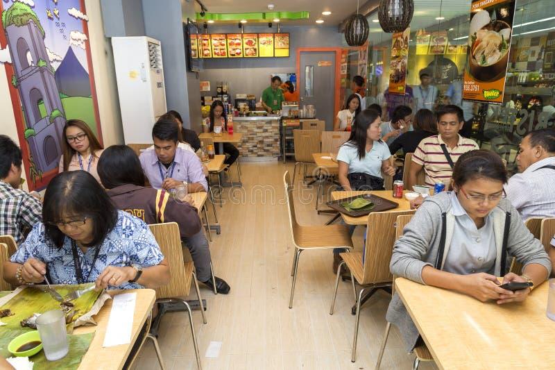 Manila Filippinerna - Juli, 26, 2016: Folk som äter lunch i en populär filippinsk snabbmatkedja arkivfoto
