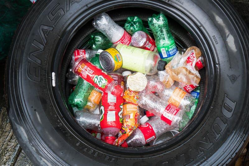 Manila Filippinerna - Oktober 2, 2018: använt gummihjul som fylls med använda plast- flaskor royaltyfri fotografi
