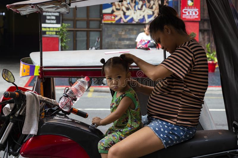 Manila, the Philippines - 14 April 2018: Mother making hair to little daughter on tricycle. Poor filippino family royalty free stock image