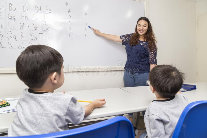 A female English teacher teaching two little boys, explaining ABC alphabet on board in classroom at school royalty free stock photo