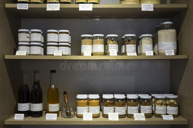 Manila, Philippines - August, 4, 2016: Wooden shelves in a shop full of jars and bottles with natural organic products.  stock photo