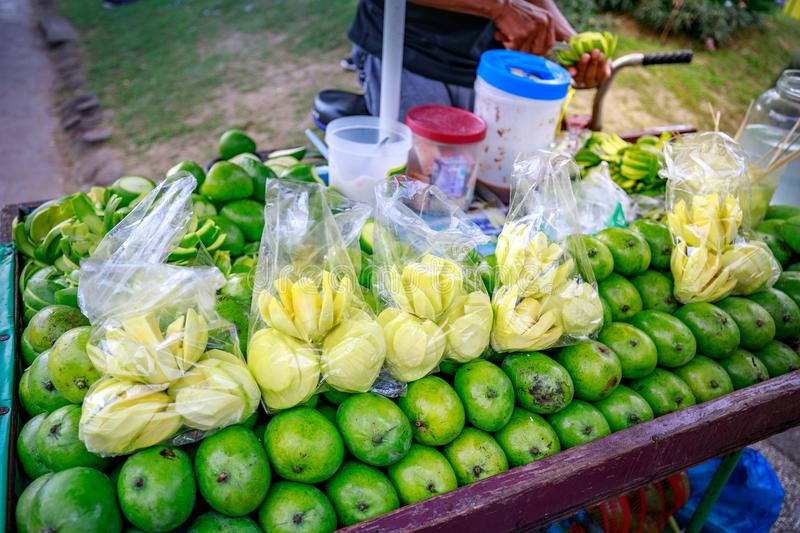 A street food vendor slices fresh green mango which sells on foo. Manila, Philippines - Feb 4, 2018 : A street food vendor slices fresh green mango which sells royalty free stock photography