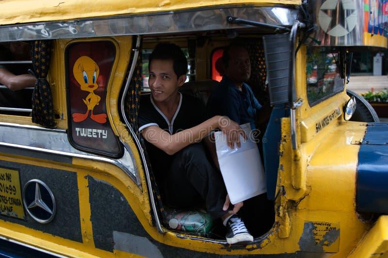 MANILA, PHILIPPINES - JANUARY 25,2012: Man sits jeepney rolling stock image