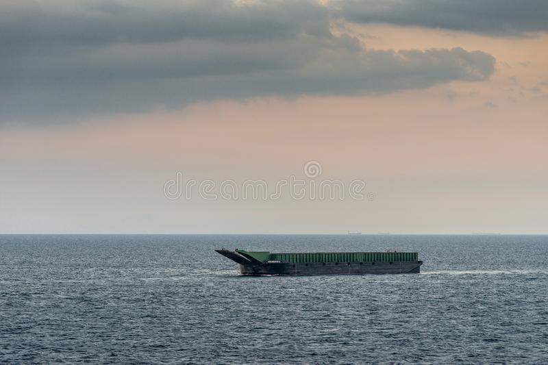 Kalusugan 2 large barge anchored off South Harbor, Manila, Philippines. Manila, Philippines - March 5, 2019: Closeup. Evening falls on green and black large stock photos