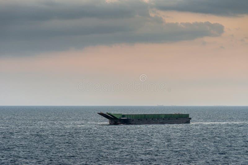 Kalusugan 2 large barge anchored off South Harbor, Manila, Philippines. Manila, Philippines - March 5, 2019: Closeup. Evening falls on green and black large stock photos