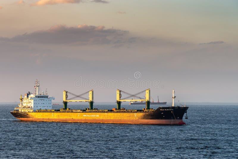 Pola Elisaveta sails under sunset light to South Harbor, Manila, Philippines. Manila, Philippines - March 5, 2019: Evening twilight shines on black and red Pola stock photos