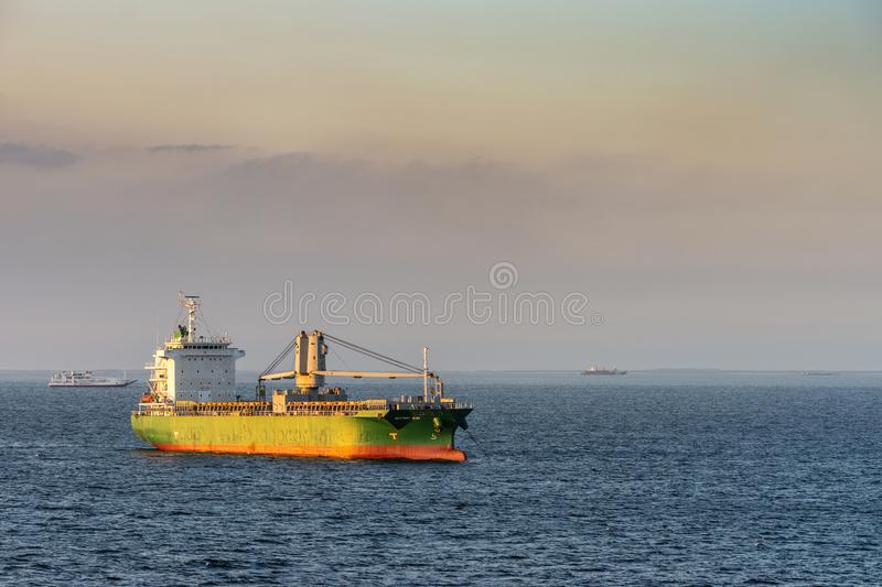 Westwind Bliss sails under sunset light to South Harbor, Manila, Philippines. Manila, Philippines - March 5, 2019: Evening twilight shines on green and red stock image