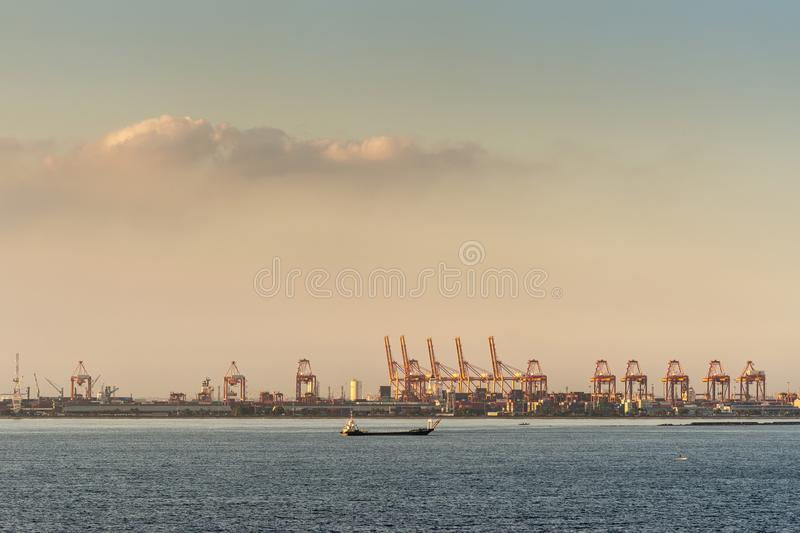 Wide shot from sea of Container Terminal in Harbor, Manila, Philippines. Manila, Philippines - March 5, 2019: Evening twilight shines on multiple red container stock image