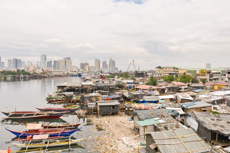 Manila slums on the background of a big city. Houses and boats of the poor inhabitants of Manila. Contrast social strata. Manila slums on the background of a big stock photos