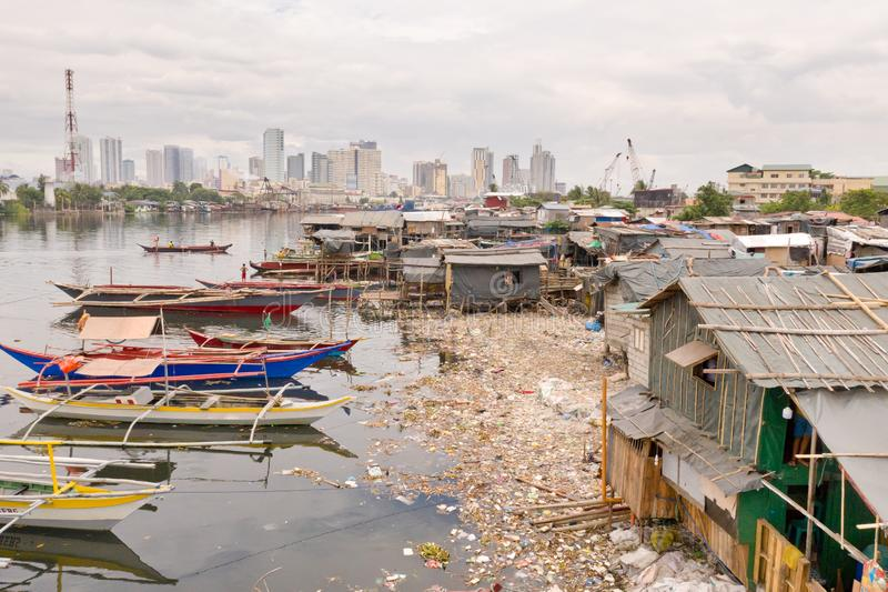 Manila slums on the background of a big city. Houses and boats of the poor inhabitants of Manila. Dwelling poor in the Philippines royalty free stock photos