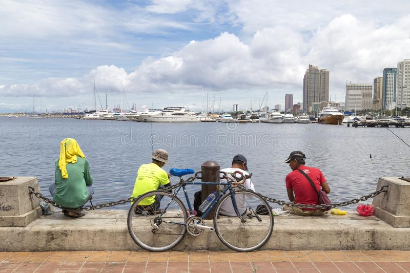 Manilla, Philippines - August 7, 2016: Men are fishing in Manila bay. Harbour Square stock images