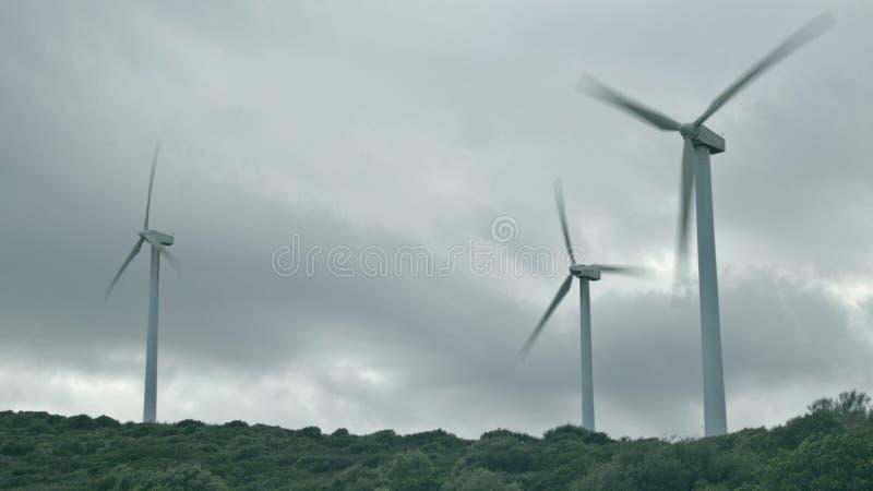 MANILVA, SPANJE - SEPTEMBER 27, 2018 Werkende windturbines op een bewolkte dag stock afbeeldingen