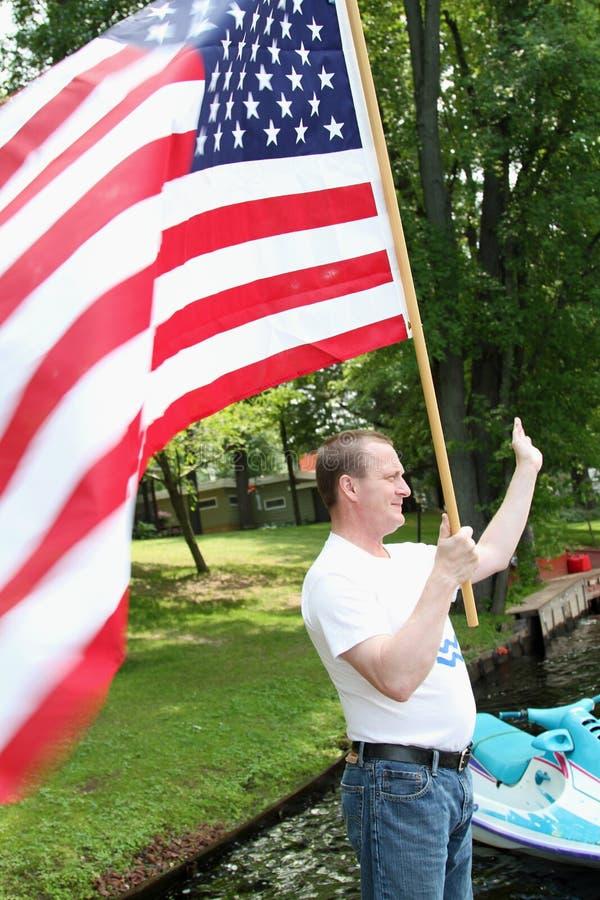 Maninnehav och vinka bölja amerikanska flaggan på skeppsdocka, som han firar självständighetsdagen, fjärdedelen av Juli arkivbilder