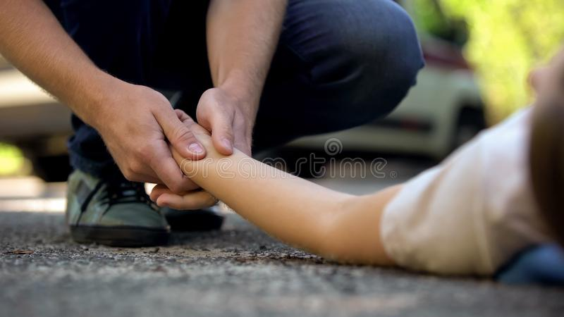 Maninnehavhand av flickan som ligger på vägen, medvetslöst offer av bilolycka, 911 royaltyfri fotografi