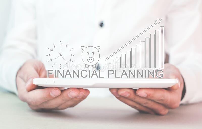 Maninnehavklocka med spargrisen och den finansiella grafen finansiellt royaltyfri fotografi