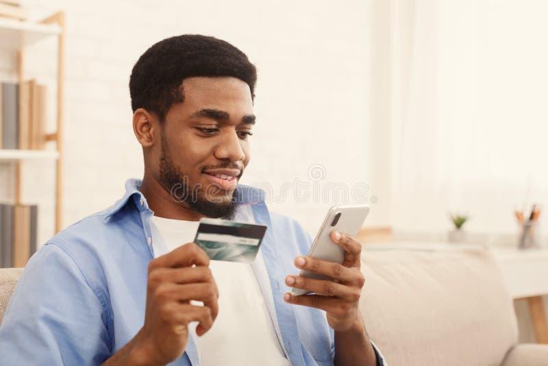 Maninnehavkreditkort och användasmartphone för online-shopping arkivbilder