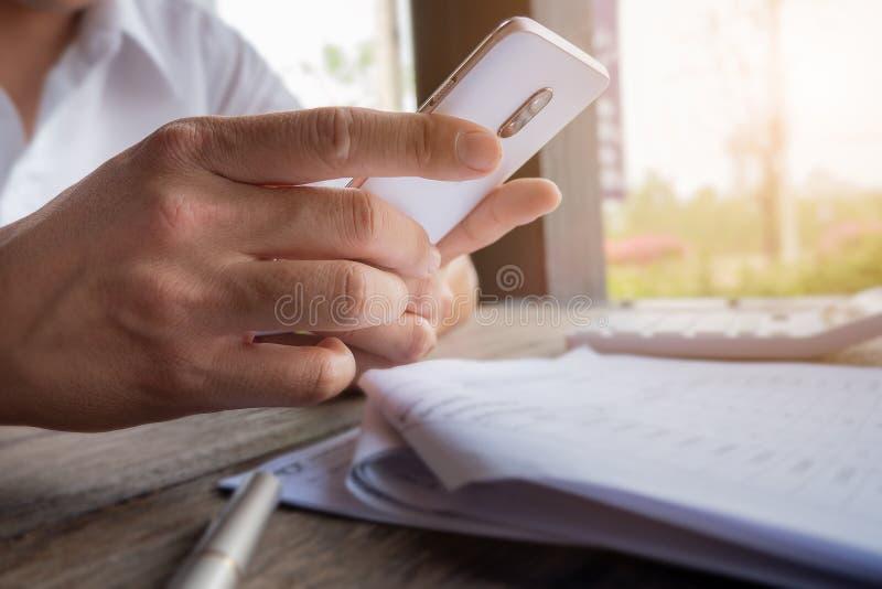 Maninnehavmobil i handen som läser text på mobiltelefonen royaltyfri fotografi