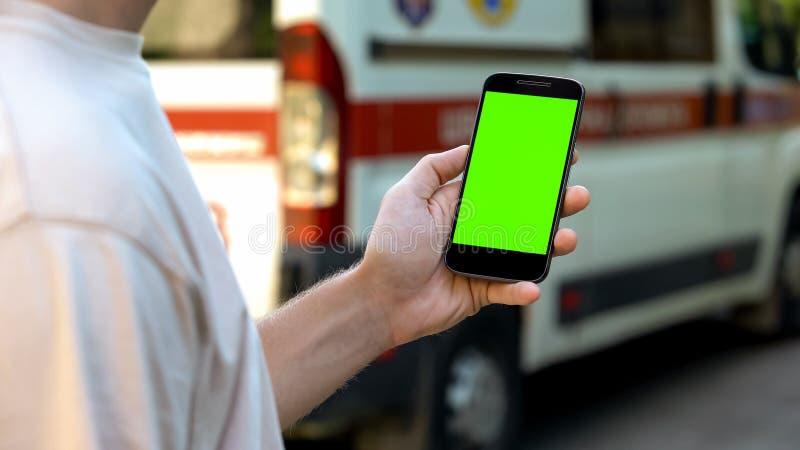 Maninnehavsmartphone, ambulans på bakgrund, online-medicinsk konsultation royaltyfri bild