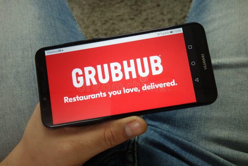Maninnehavsmartphone med Grubhub Inc logo för rengöringsdukkommersplattform arkivbilder