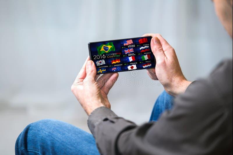 Maninnehavtelefon i händer som håller ögonen på på en kanal av sportar på TV fotografering för bildbyråer