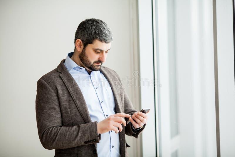 Maninnehavtelefon - ung affärsman som i regeringsställning använder smartphonen arkivbild