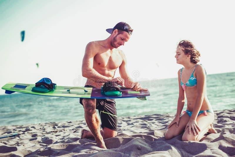 Maninstruktören undervisar flickan, i att surfa för drake royaltyfria bilder
