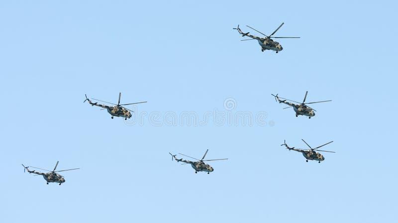 Maniobras militares de los helicópteros en el cielo azul fotografía de archivo